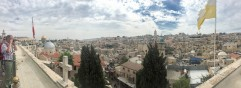Panorama of the Old City from the Austrian Hospice in the Muslim Quarter. Dome of the Rock is the gold dome on the left. Church of the Holy Sepulchre is left of the yellow/white flag and right of the tower -- two low domes on the horizon.