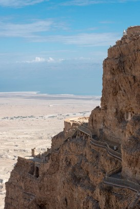 Two of the hanging palaces on Masada. The third palace is at the top (there is a person standing on a fenced platform on the top)